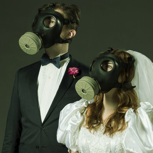 Apocalypse Sebastien Archibald and Claire Hesselgrave in wedding garb and gas masks. Photo-by-Emily-Cooper