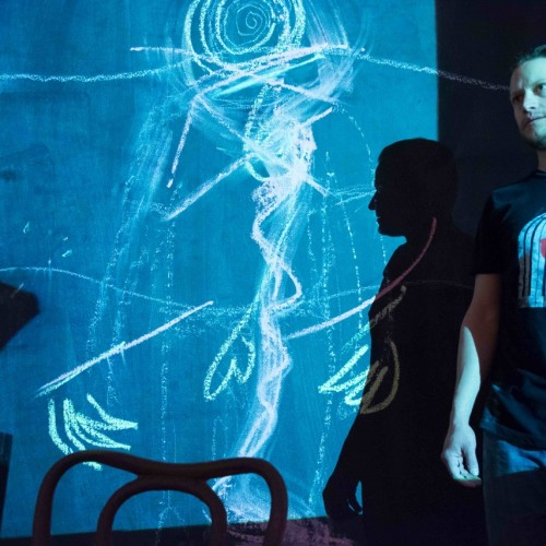 This Stays in the Room Remount: Man standing in front of neon blue projection of hand-drawn squiggles