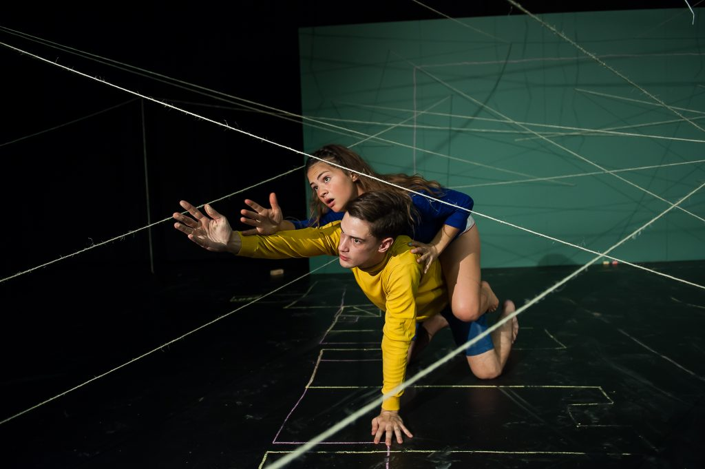 Young woman and young man kneeling amidst a 3-D blueprint