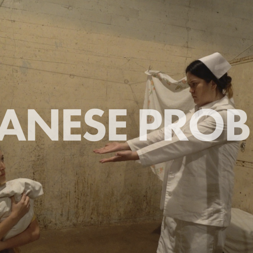 Image of nurse gesturing for seated mother to give over the baby in swaddling clothese that she is holding - in Japanese Problem