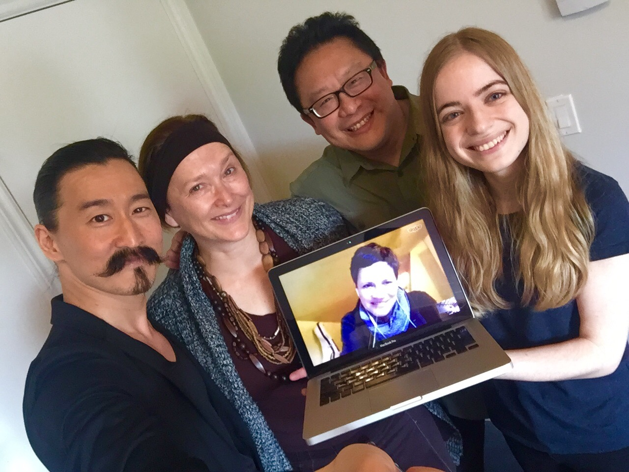 Tetsuro Shigematsu, Leanna Brodie, Jovanni Sy, Veronique West holding up computer with Kendra Fanconi on screen