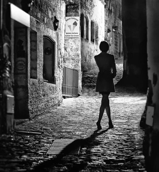 Black and white image of female/trans woman waling up a cobblestone alley at night