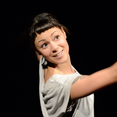Amber Funk Barton - woman of colour with black hair and short bangs, in dance pose, one arm forward