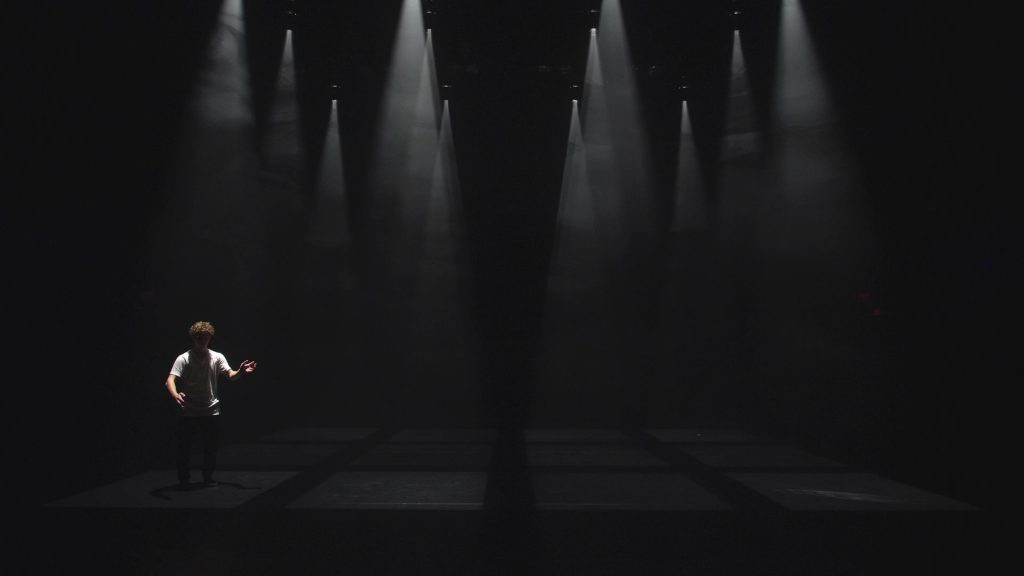 Dancer Isak Enquist in How to Say Goodbye – long shot of large darkened stage with ghostly spotlights shining down on the stage