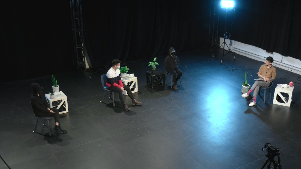 Our three speakers and Derek during Unscripted: yellow objects' Fifth-Estate-style interview - seen in an aerial view, each speaker separated by 6 ft of space and masked or shrouded in dark obscuring clothing, and Derek positioned in a chair off the right. All have a small white end table beside them with a plant on it