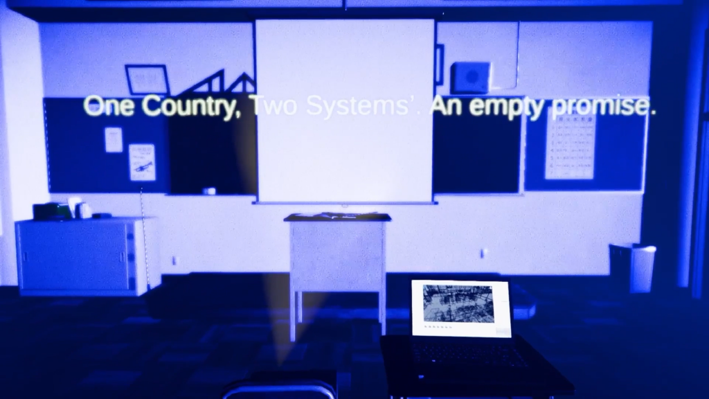 """A yellow objects game play design test presented at the livestream depicting a model of a classroom in blue tones with a desk at the centre, whitebaord and calendar on the wall behind and a credenza and waste basket on opposite sides, with the words: """"One Country, Two Systems. An empty promise."""""""