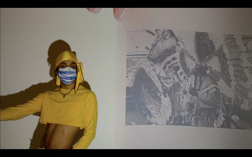 Performer in long sleeve yellow crop top, yellow head scarf, blue and white face mask with black and white wall projections to their side