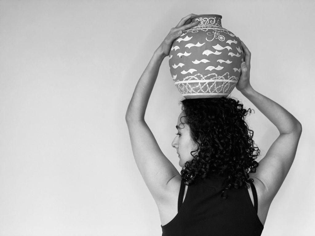 María Escolán back & face profile: medium length black curly hair, black sleeveless top, holding a ceramic jar on her head with both arms