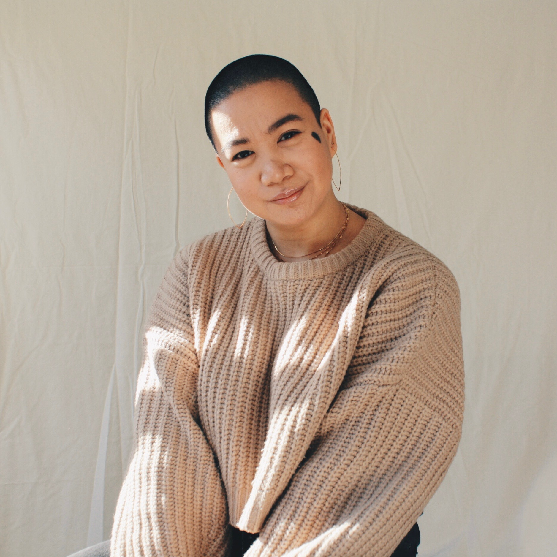Kamila, a Filipinx woman with a shaved head and an oval birthmark on her left cheek, smiles in front of a white background. Sunshine glints across her face and gold jewellery, creating a mosaic of shadow and light across her light brown sweater.
