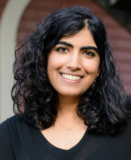 Woman of South Asian descent with shoulder-length black hair and bright smile