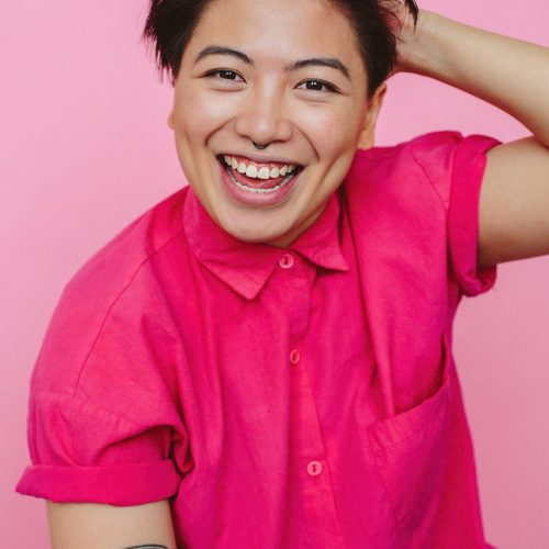 Headshot of Jesse wearing a fuchsia coloured short-sleeved-shirt with visible tattoo on right arm. They are smiling with hand at the back of head of short black hair.