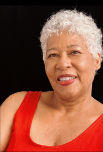 Celeste Insell headshot: woman with short white hair wearing a red tank and matching red lipstick