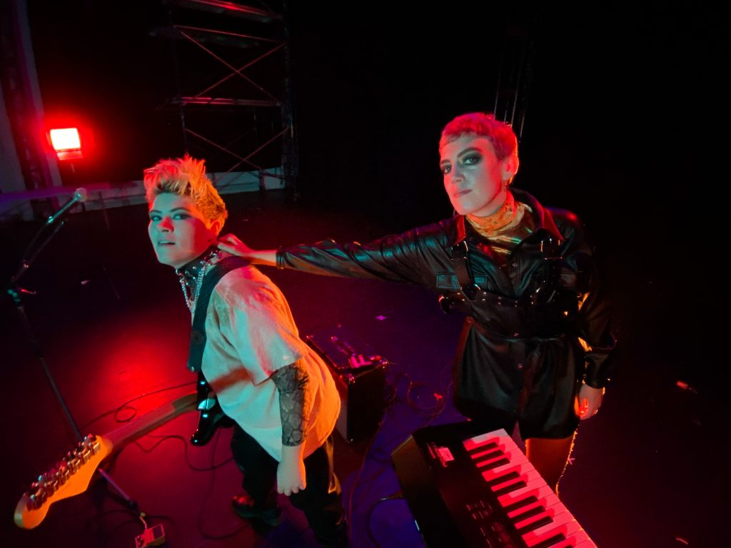 Promotional photograph featuring two queer punk musicians.