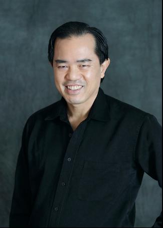 Kagan headshot: short black hair, burgundy button-down shirt, smiling at camera